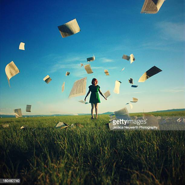 Girl in field surrounded by book pages
