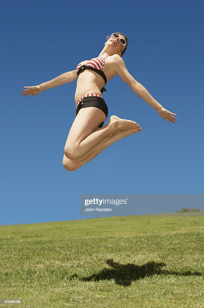girl in fifties style bikini jumping in the air : Stock Photo