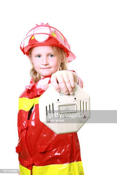 Girl in firefighter uniform displaying a smoke detector