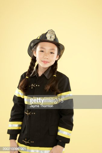 Girl (8-10) in fireman costume smiling, portrait