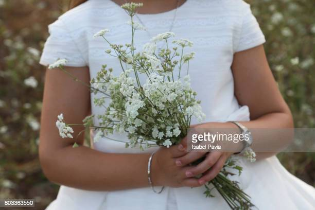 Girl in First Communion Dress Holding Wild Flowers