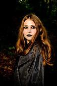 Pretty young girl with black make up portrait in forest
