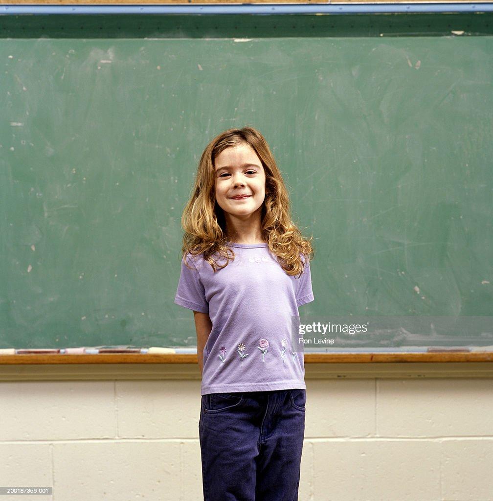Girl (9-11) in front of blackboard, portrait