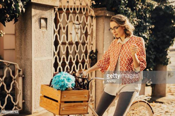 Girl in front of house sitting on the bicycle
