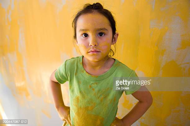 Girl (4-6) in front of painted wall, portrait