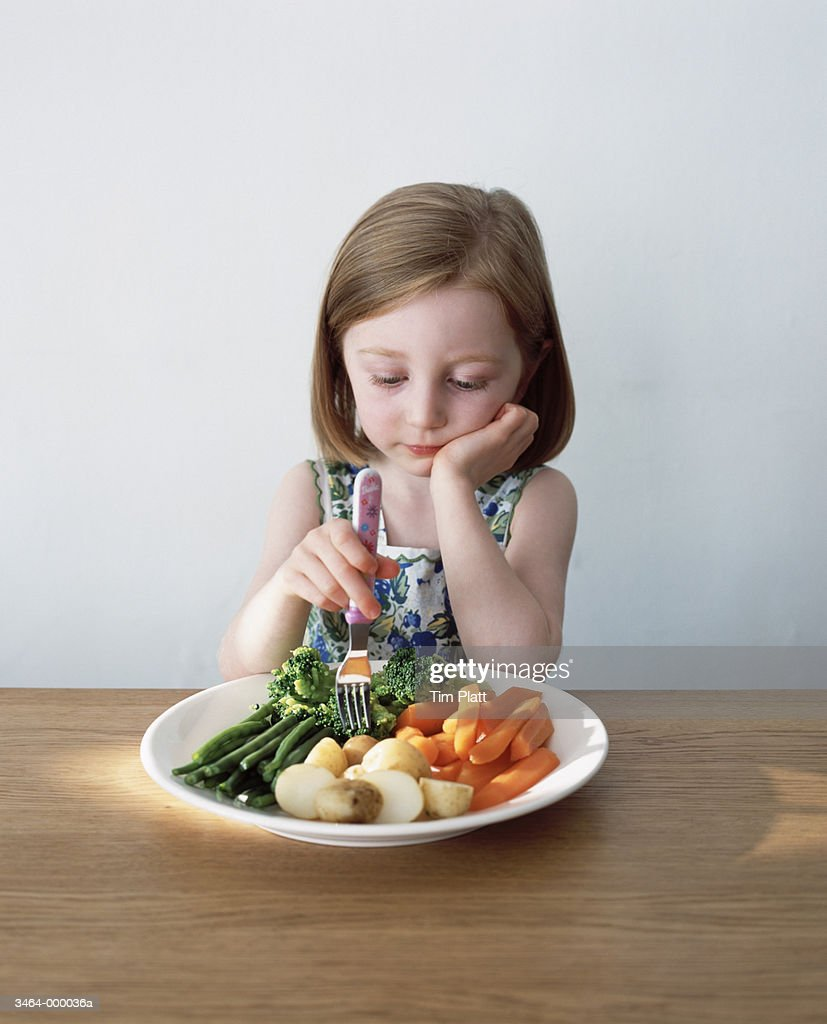 Girl in Front of Plate of Food : Stock Photo
