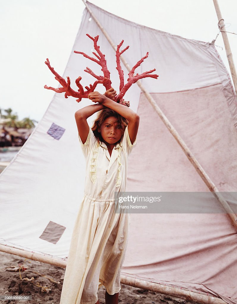 Girl (9-11) in front of tent holding red coral above head : Stock Photo