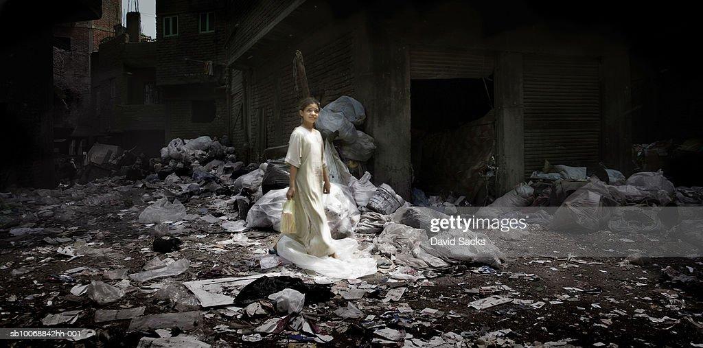 Girl (6-7) in garbage strew alley : Stock Photo