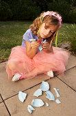 Girl (6-8) in garden piecing together broken crockery