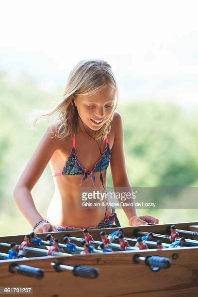 Girl in garden playing table football, Buonconvento, Tuscany, Italy