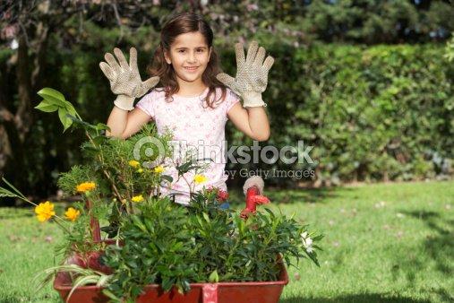 Girl In Garden Wearing Gardening Gloves Hands Up Smiling