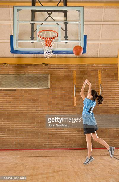 Girl (10-12) in gym shooting basketball, side view