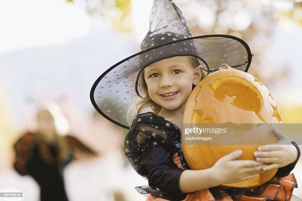 Girl in Halloween costume with jack-o'-lantern : Stock Photo