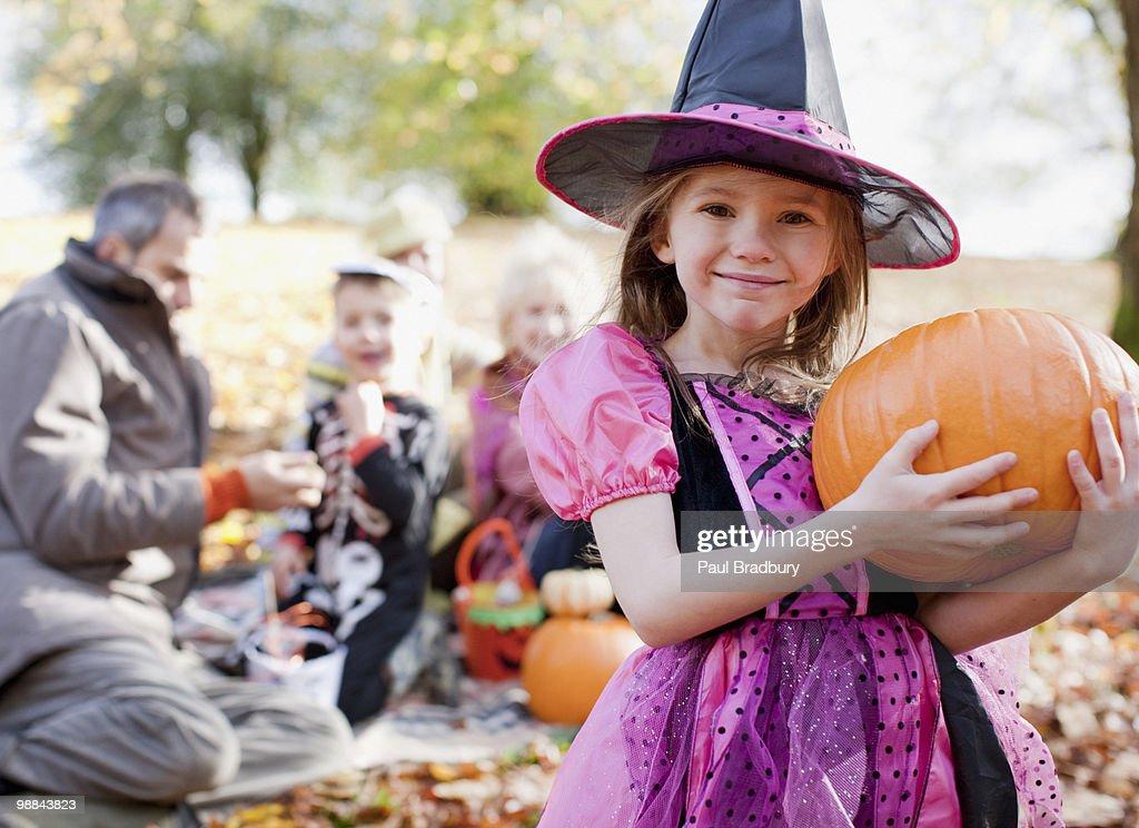 Girl in Halloween costumes holding pumpkin : Stock Photo