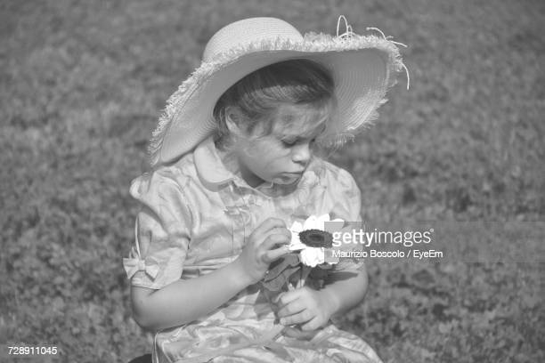 Girl In Hat Holding Flower On Field During Sunny Day