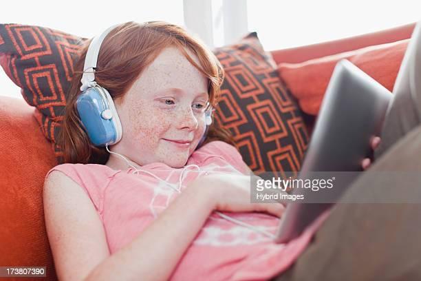 Girl in headphones using tablet computer
