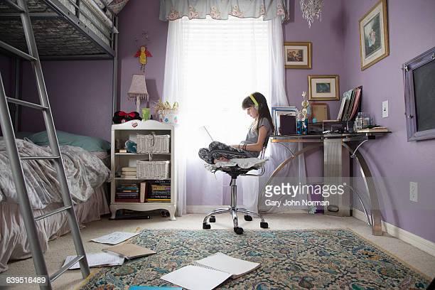 Girl in her bedroom using laptop with headphones