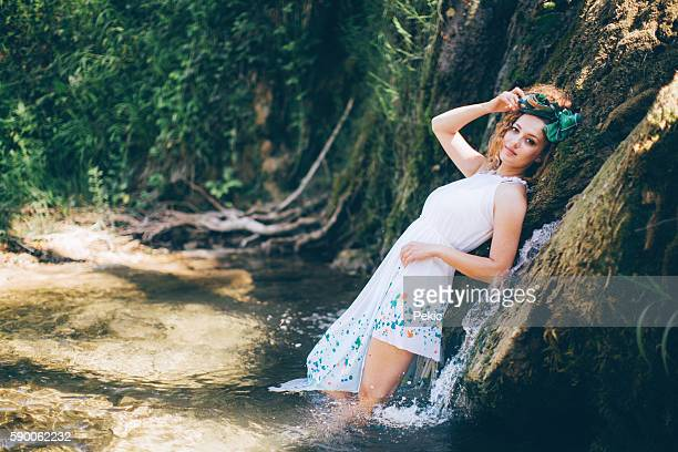 Girl in hippie spring colorful dress in waterfall