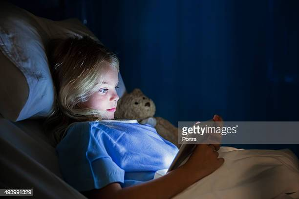 Girl in hospital bed using digital tablet.