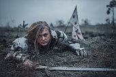 Girl with wounds on her face in image of Jeanne d'Arc in armor crawls in mud with sword in her hands on background of flag.