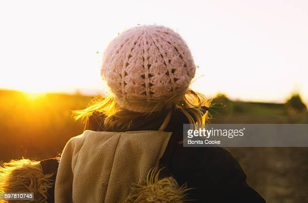 Girl in jacket, walking, looking at sunset