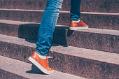 A girl in jeans and beautiful leather shoes steps over the marble steps of the staircase