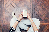 Girl in jeans sitting on the floor at home and using a mobile phone, a top view