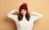 Funny Hipster Girl in Knitted Sweater and Beanie Hat over beige soft Background. Trendy Casual trendy young woman in winter outfit