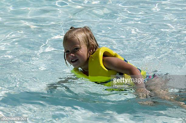 Girl (4-5) in life-jacket floating in pool