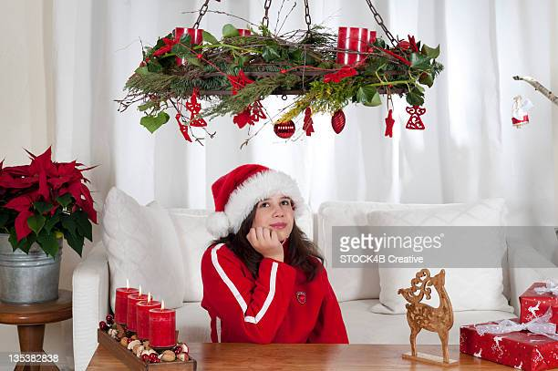 Girl in living room with Christmas decoration looking up