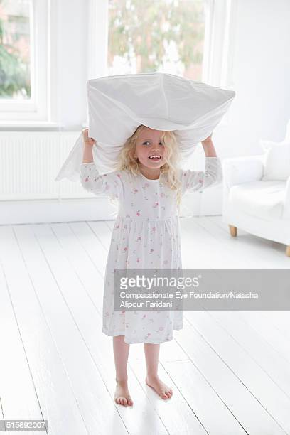 Girl in living room with pillow on her head