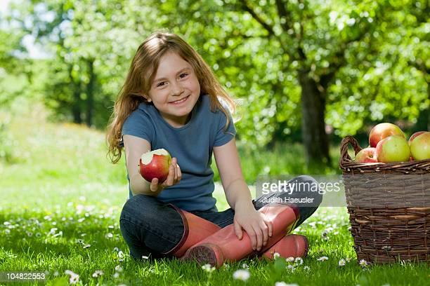 Girl in meadow, eating apple