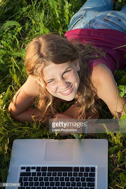 Girl (12-13) in meadow using laptop, elevated view