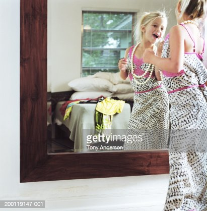 Girl (6-8) in mother's dress applying lip gloss in mirror : Stock Photo