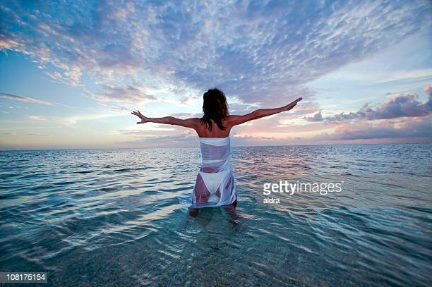 Girl in ocean at Sunset