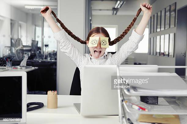 Girl in office with adhesive notes covering eyes holding plaits