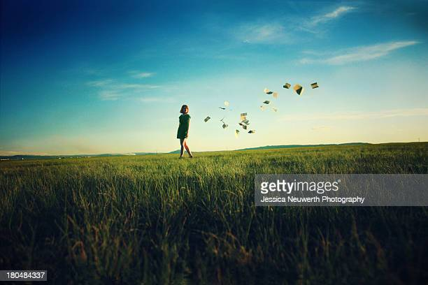Girl in open field with a trail of book pages