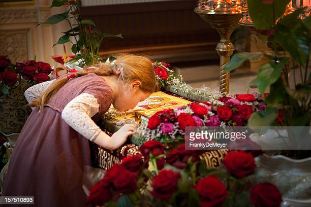 Girl in orthodox church, kissing icon for Easter celebration