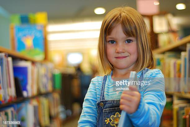 Girl in overalls showing off her book in the library