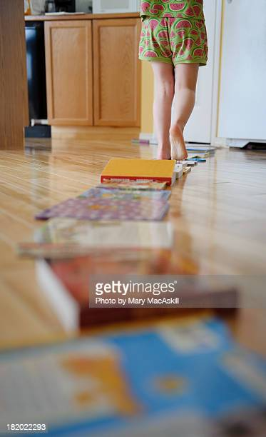 Girl in Pajamas Walking on Books