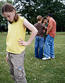 Girl (9-11) in park hand on hip, looking down, boys (9-12) in background