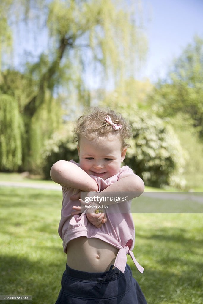 Girl (21-24 months) in park, smiling, close-up