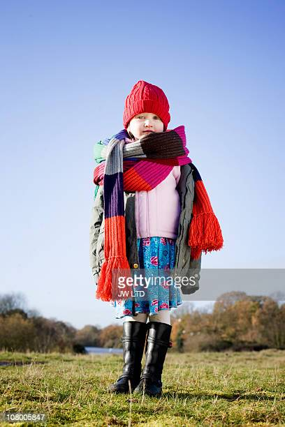 Girl in park wearing long knitted scarf, portrait