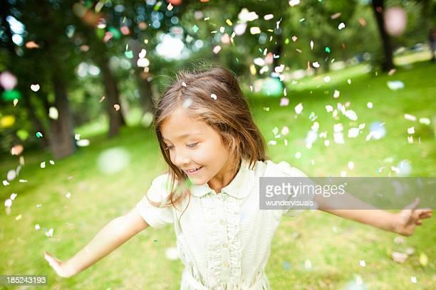 Mädchen im Park mit bunten Konfetti fallen auf Ihrem