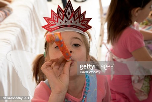 Girl (6-7) in party hat blowing party horn blower, elevated view : Stock Photo