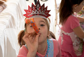 Girl (6-7) in party hat blowing party horn blower, elevated view
