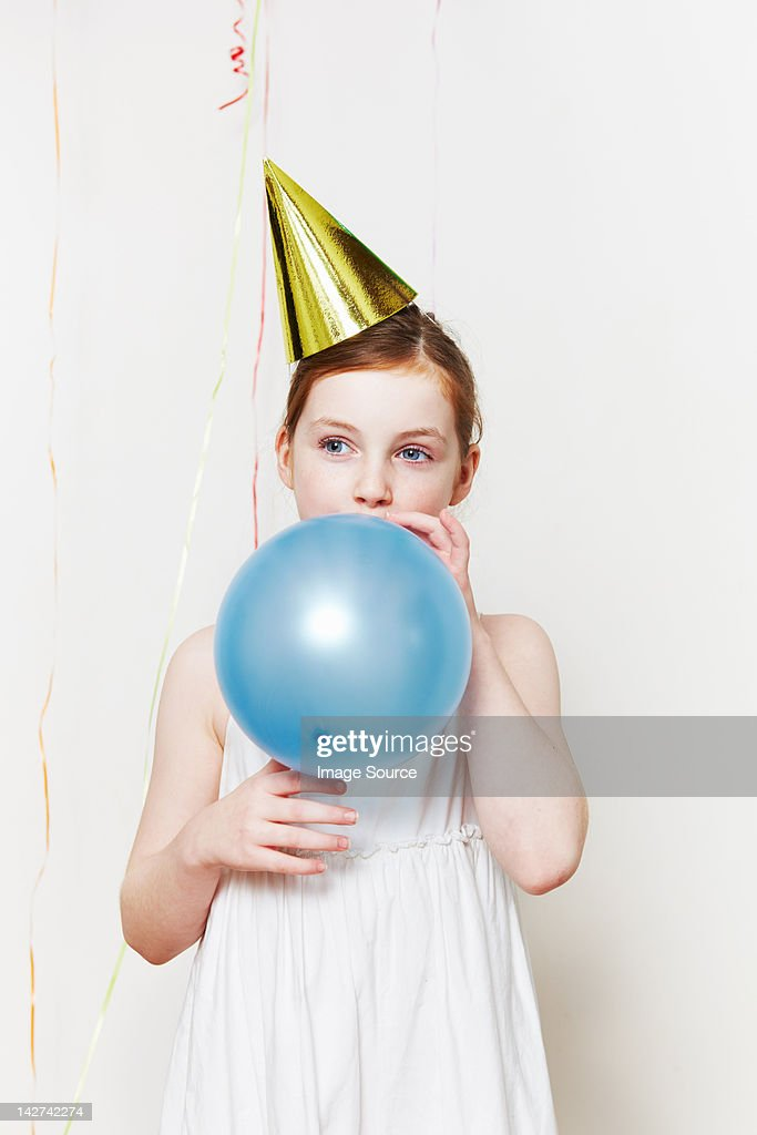 Girl in party hat, blowing up balloon : Stock Photo
