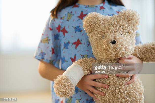 Girl in patient gown with teddy bear