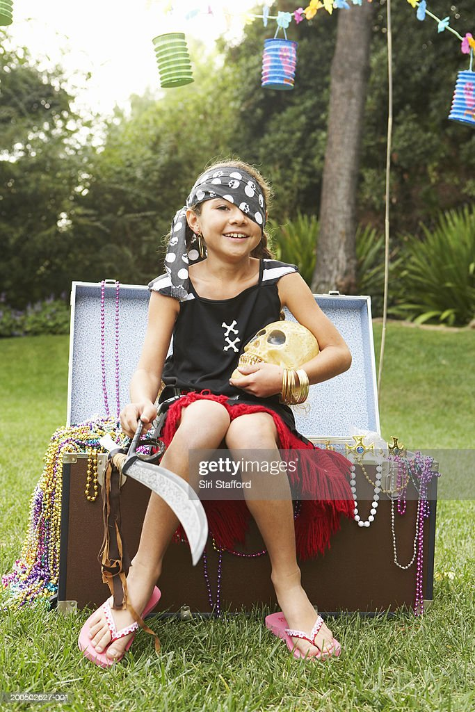 Girl (8-10) in pirate costume sitting on faux treasure chest : Stock Photo