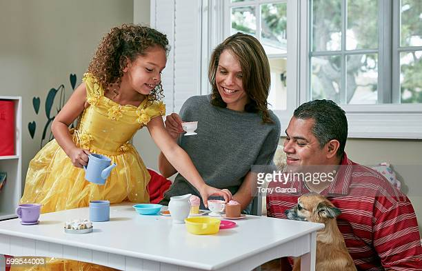 Girl in playroom sitting at table serving tea from toy tea set to parents